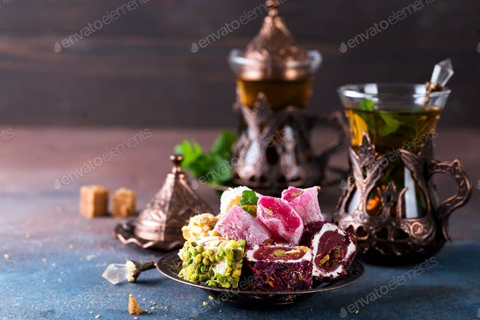 Traditional turkish sweets with tea mint in a traditional glass on a concrete background