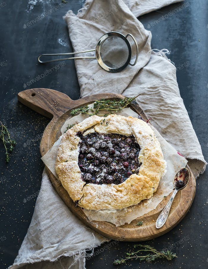 Homemade crusty pie or galette with blueberries, thyme and ice-cream