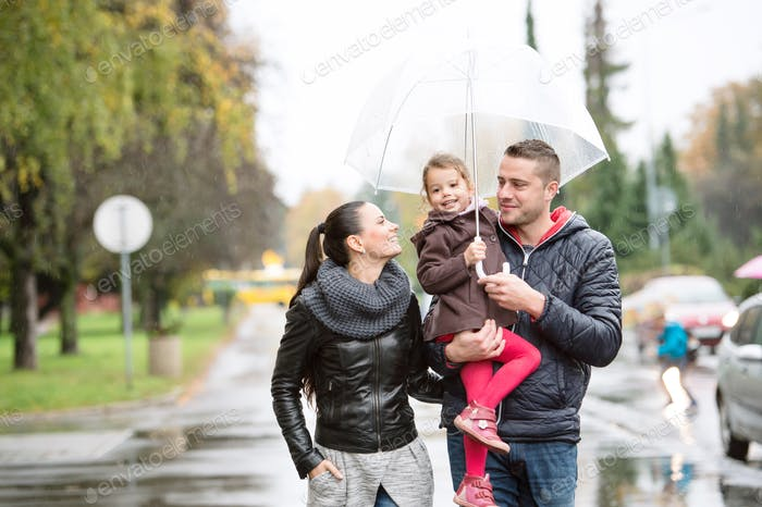 Family with daughter under the umbrellas Walk on rainy day.