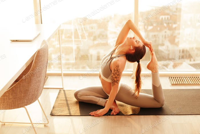 Beautiful woman in sporty top and leggings sitting and training yoga poses at home over city view