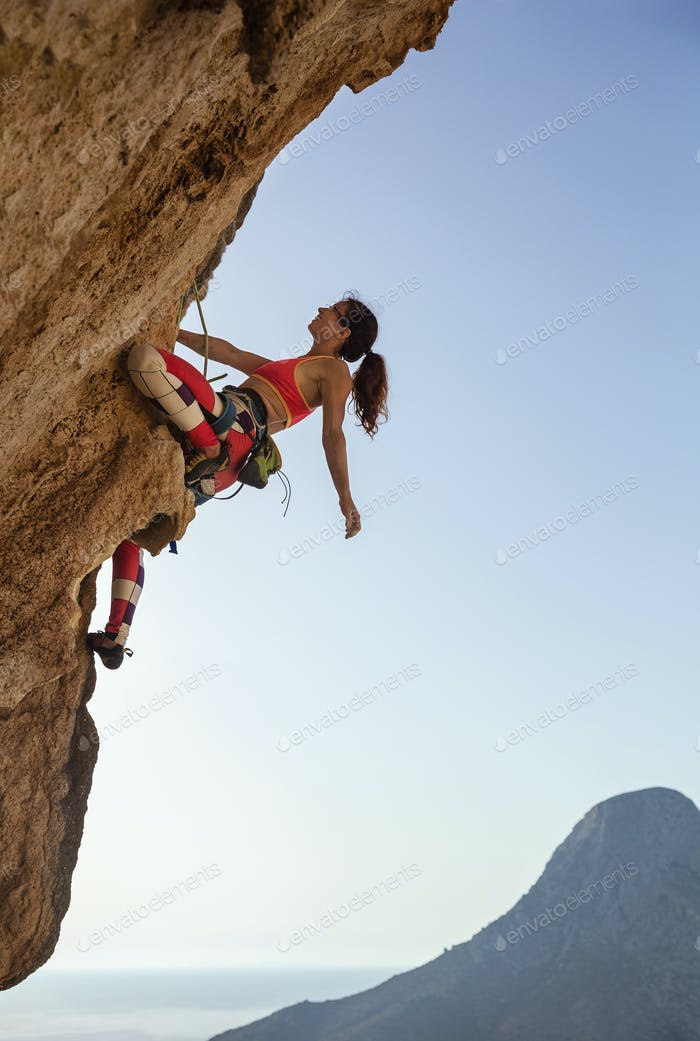 Female rock climber looking up at challenging route