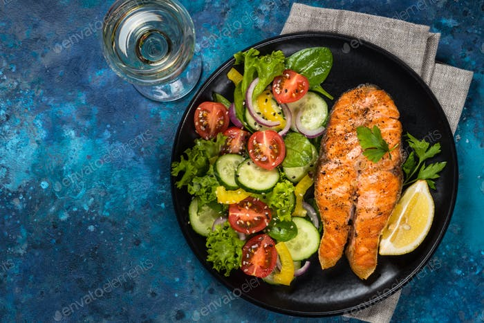 Grilled salmon fish steak with fresh vegetables salad.