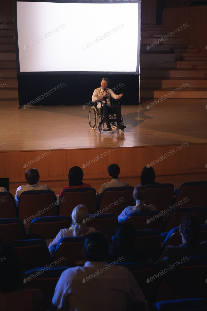 Businessman sitting on wheelchair and giving presentation to the audience in the auditorium