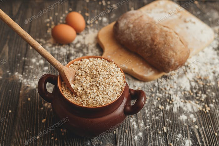 Pot filled with oatmeal on the table  a spoon, eggs and bread