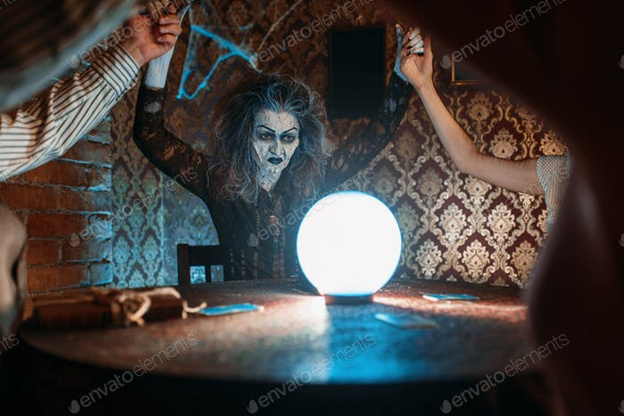 Witch over a crystal ball, young people on seance