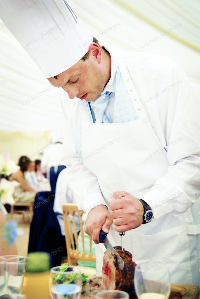 Chef Carving Rindfleisch bei einem Hochzeitsempfang Konzept