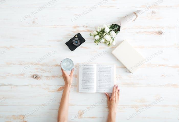 Women hands open book on the wooden desk