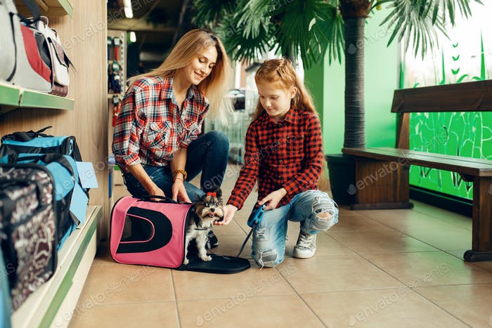 Mother with girl choosing bag for little puppy