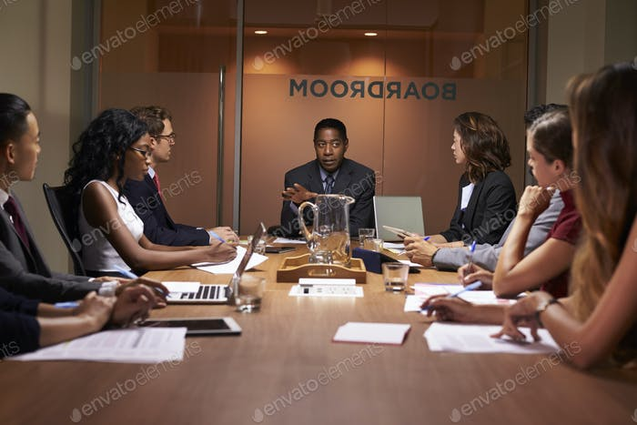 Corporate business people at an evening boardroom meeting