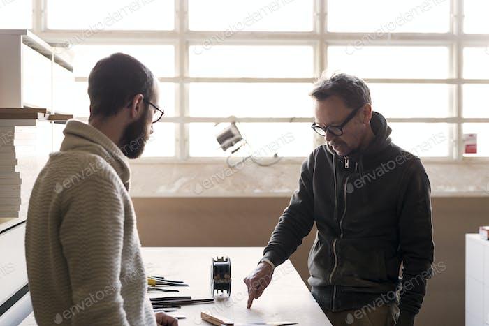 Carpenter talking to client in workshop