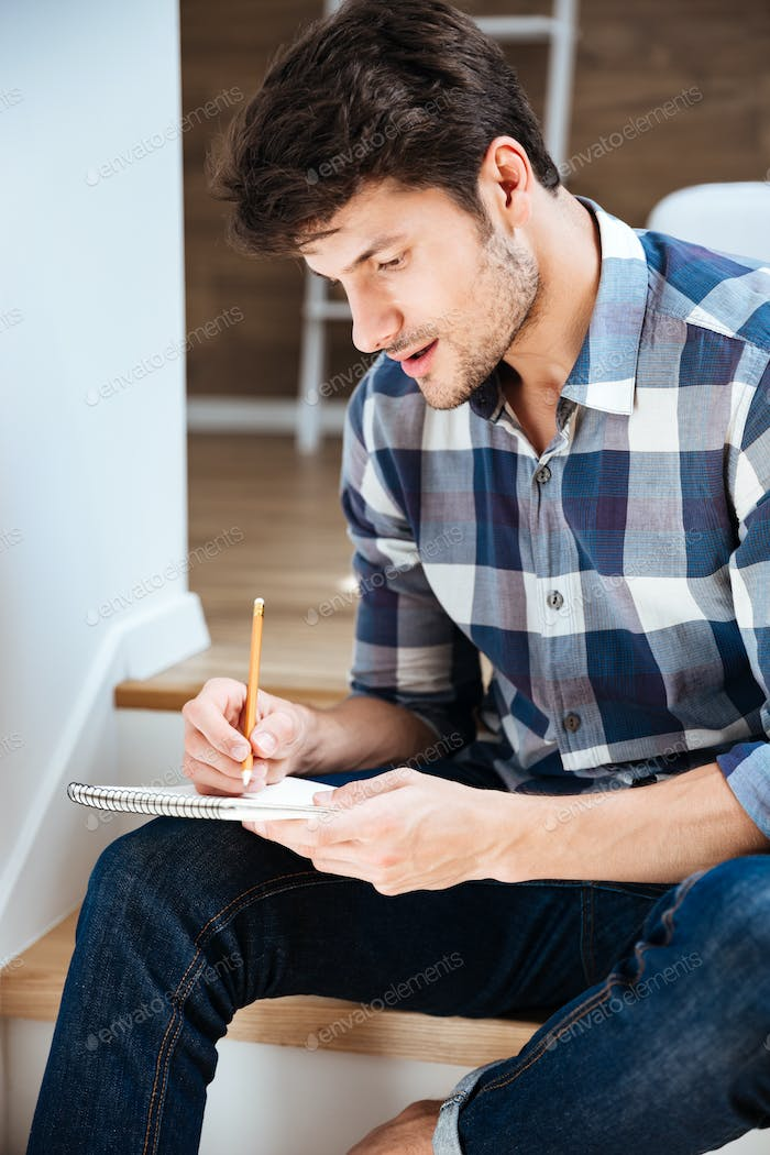 Concentrated young man sitting and writing in notepad at home