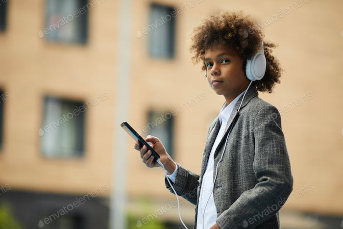 African boy with mobile phone outdoors