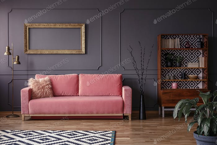 Pink settee against grey wall with mockup of gold frame in elega