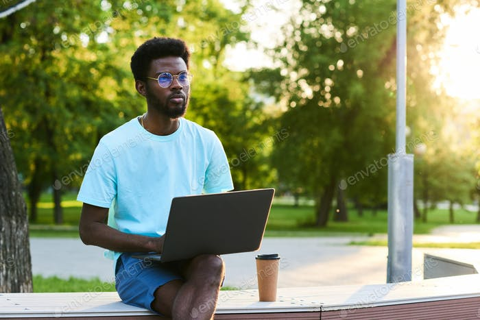 Man with computer outdoors