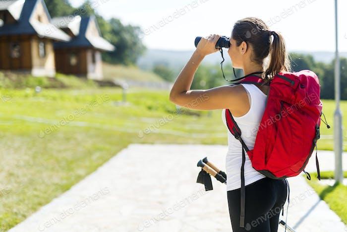 Beautiful tourist hiking and using binoculars
