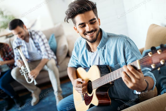 Young man playing guitar for his friends