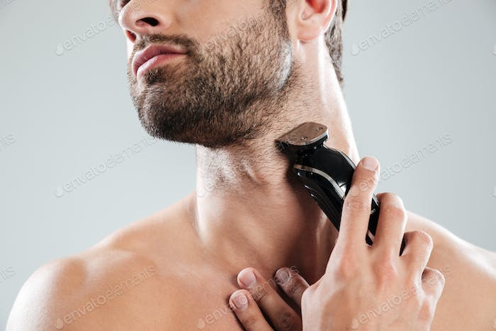Thumbnail for Cropped image of a bearded man using electric razor