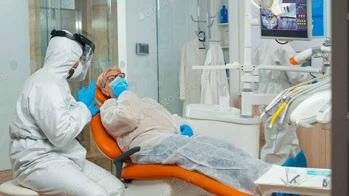 Orthodontist in protection coverall speaking to patient with toothache