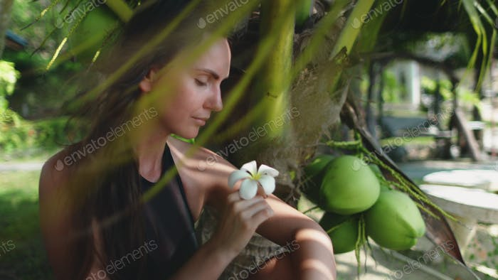 caucasian woman sitting under coconut palm tree