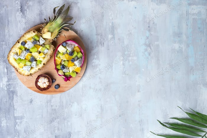 Exotic fruit salad served in half a dragon fruit and pineapple on round wooden plate on stone