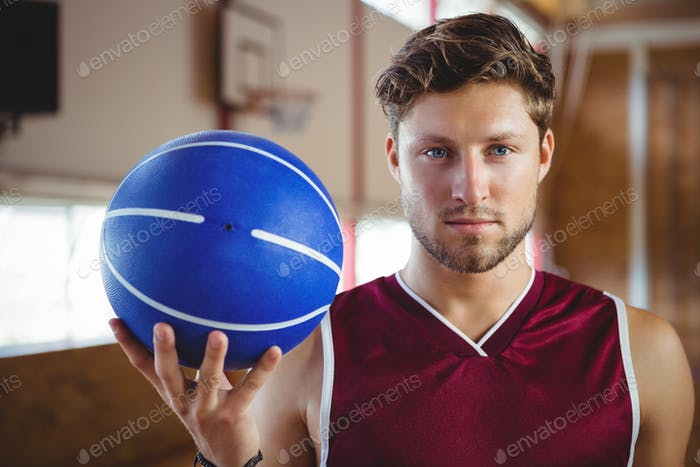 Portrait of confident player holding basketball