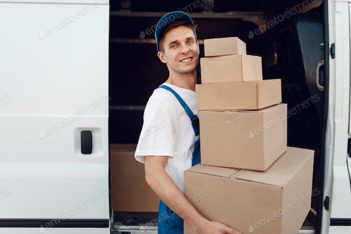 Mailman entlädt das Auto mit Paketen, Lieferung