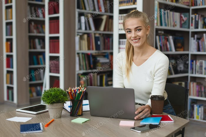 Pretty blonde girl studying with laptop at library