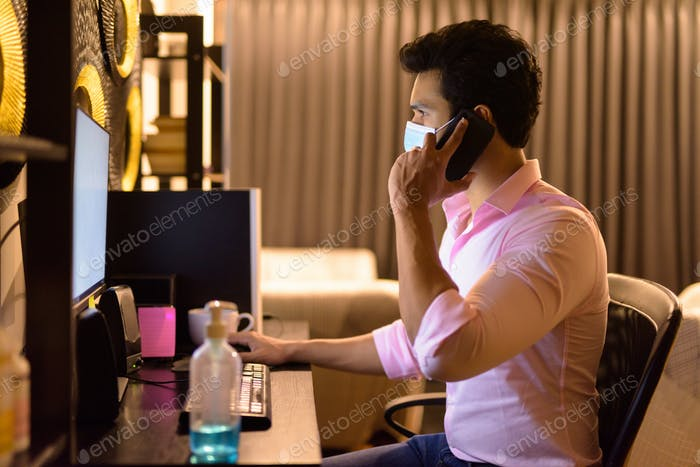 Young Indian businessman with mask talking on the phone while working overtime at home during