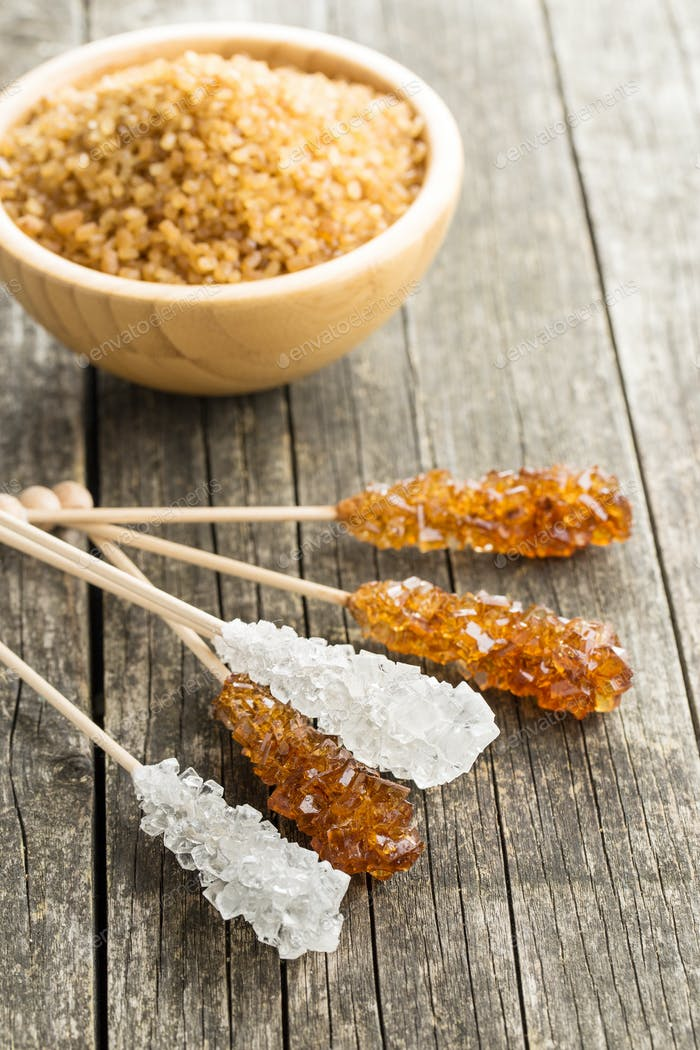 Crystalline sugar on wooden stick.