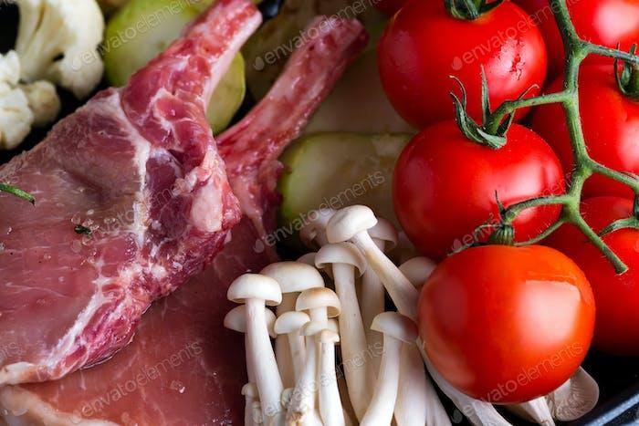 Raw lamb ribs marinating with buna-shimeji and tomato in a grill pan close-up