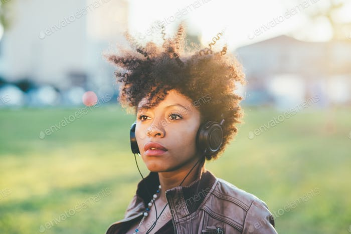 Half length of young beautiful afro curly hair woman listening m