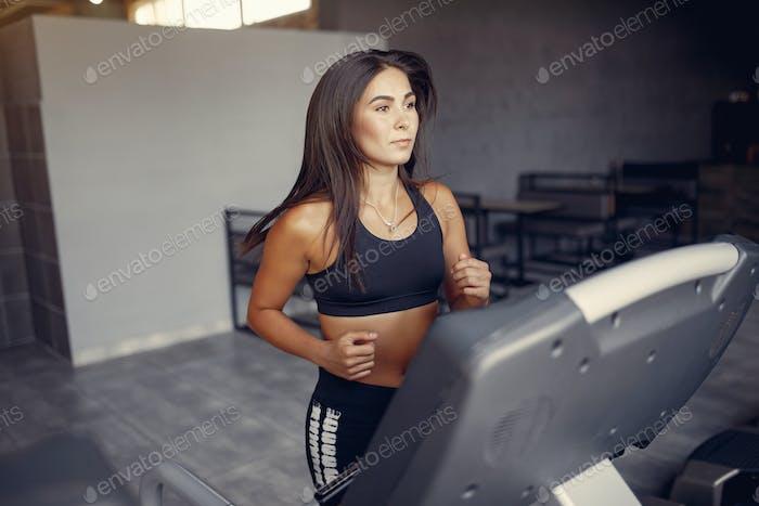 Sports brunette in a sportswear training in a gym