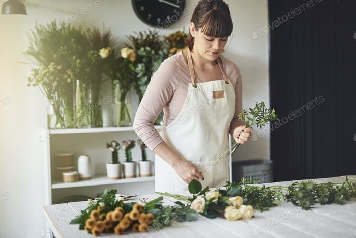 Young woman making floral arrangements in her flower shop