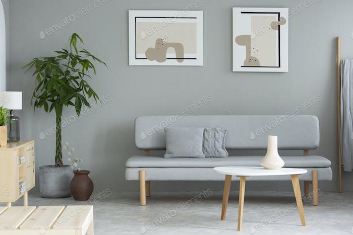 Grau Wohnzimmer Interieur in echtem Foto mit frischer Pflanze, Holz