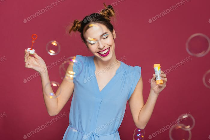 Smiling attractve young woman with soap bubbles