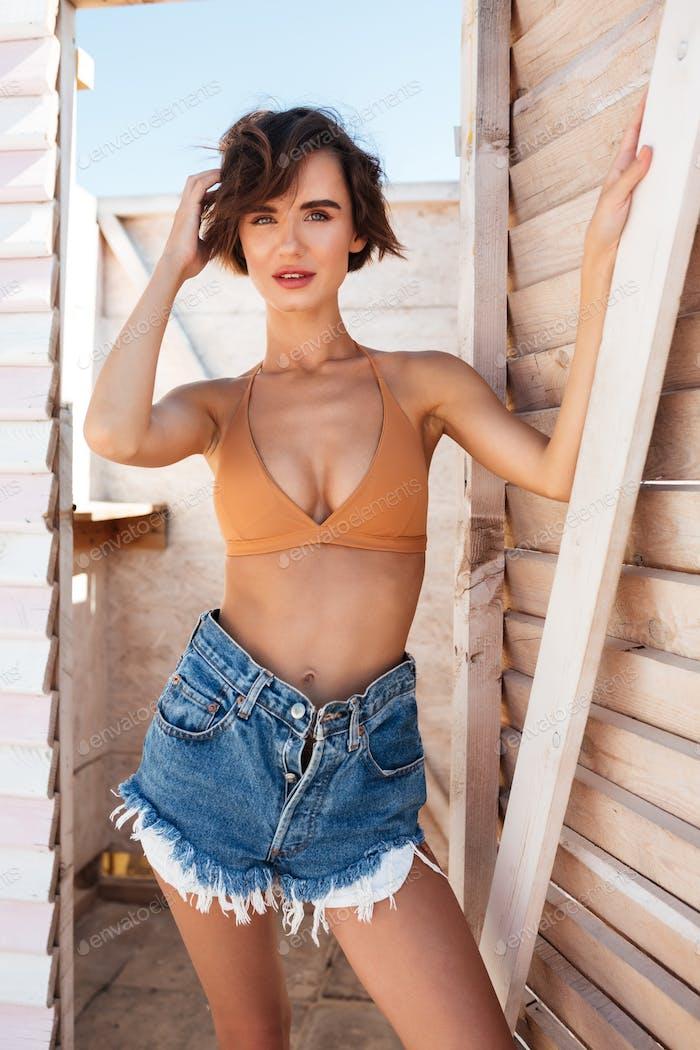 schön Mädchen posiert auf Kamera in Umkleidekabine am Strand