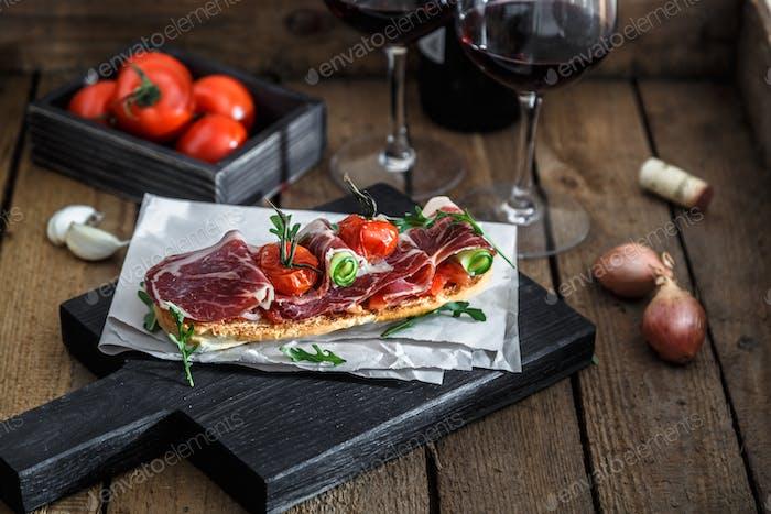 Traditioneller Parma-Schinken Antipasto auf Holzhintergrund, rustikaler Stil