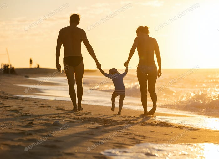 Happy family with little boy together at sunset