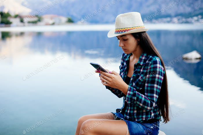 woman browsing smartphone at seaside
