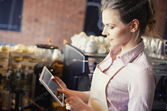 Side view of waitress with digital tablet