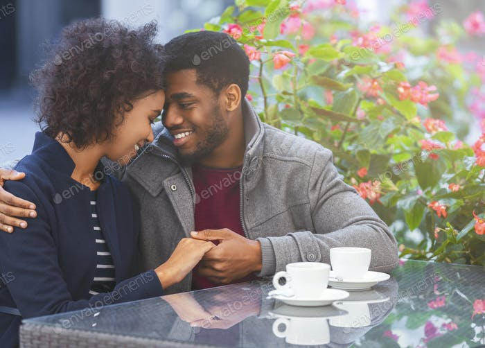 Sweet african couple holding each other hands in cafe