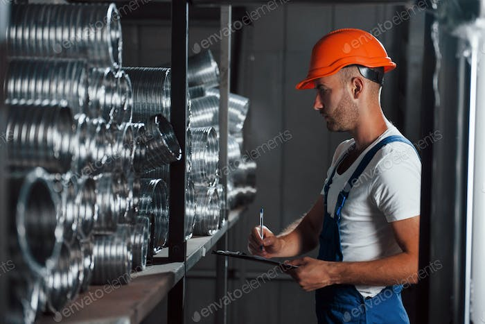 Controlling production quality. Man in uniform works on the production. Industrial modern technology