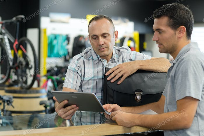 man working in bike rental shop dealing with customer