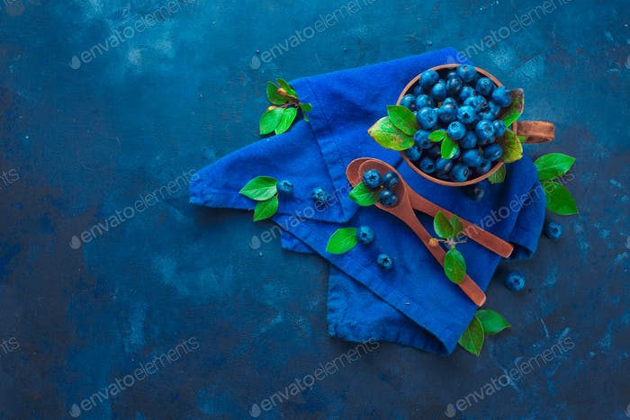 Summer berry harvest concept on a dark blue background with copy space. Blueberries in a ceramic cup