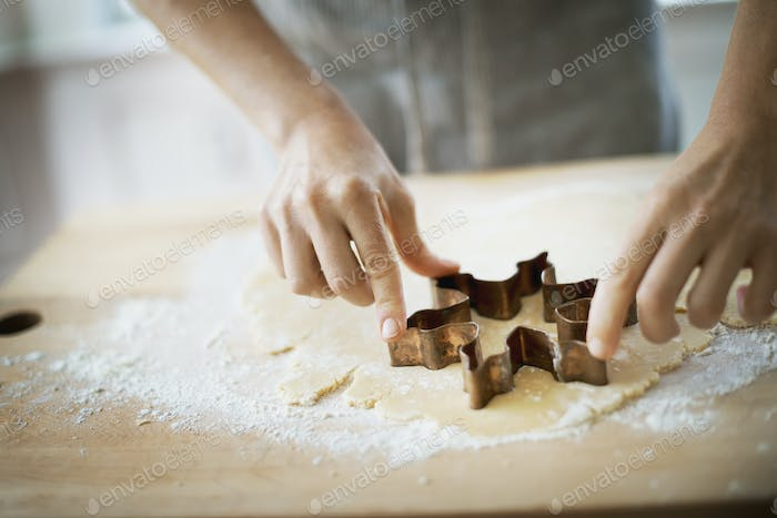 Woman making organic Christmas cookies, cutting dough with a cookie cutter.