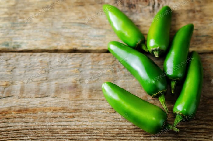 Fresh jalapeno peppers on a dark wood background