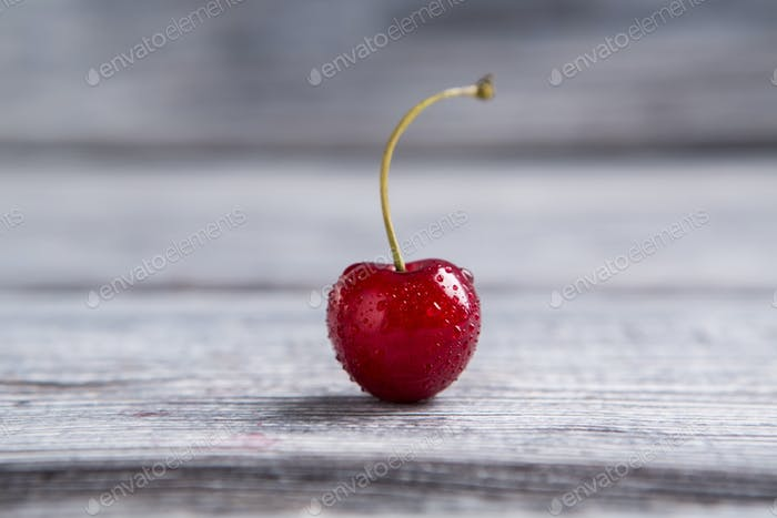 Wet cherry on gray surface