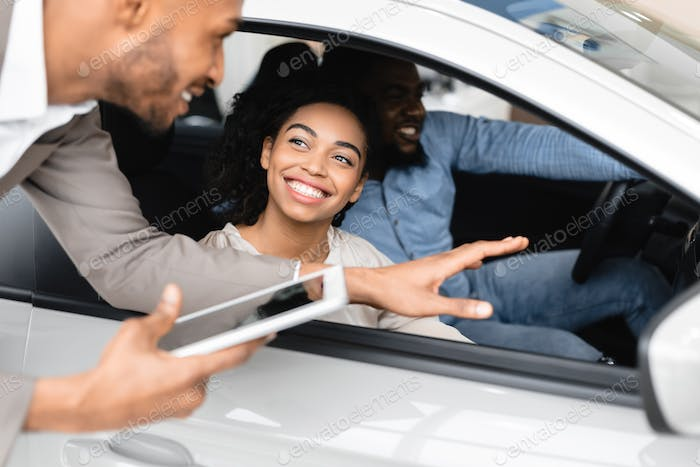 Car Buyers Choosing New Family Autombile With Seller In Store