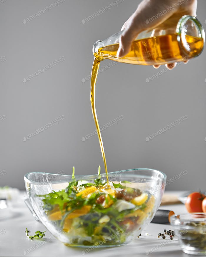 A girl's hand pours oil into a freshly prepared vegetable salad in a bowl on a gray background
