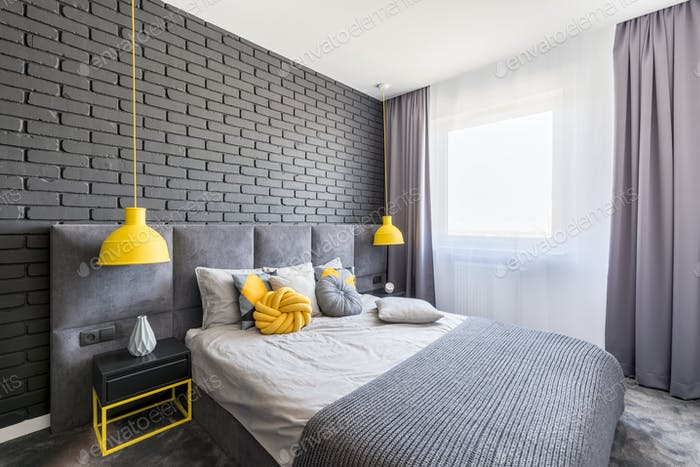Real photo of grey and yellow bedroom interior with window with